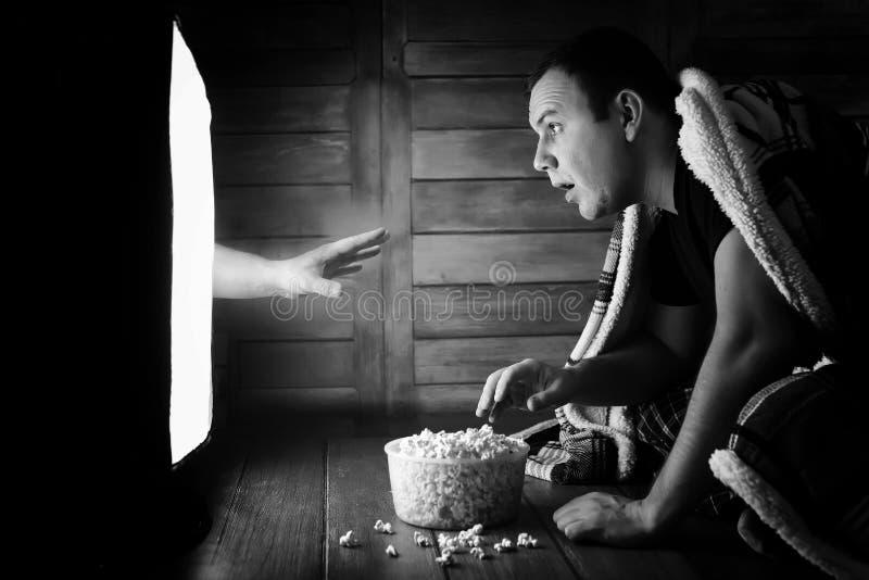 Mirando un horror en la TV blanco y negro fotos de archivo