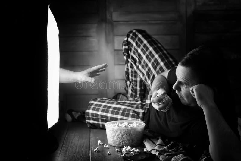 Mirando un horror en la TV blanco y negro foto de archivo libre de regalías