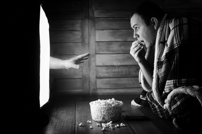 Mirando un horror en la TV blanco y negro fotografía de archivo