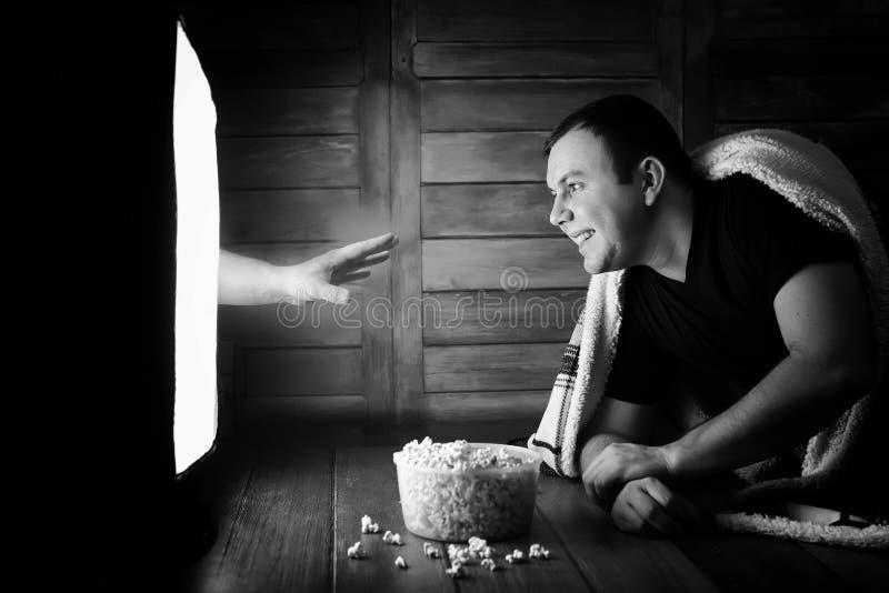 Mirando un horror en la TV blanco y negro imagen de archivo