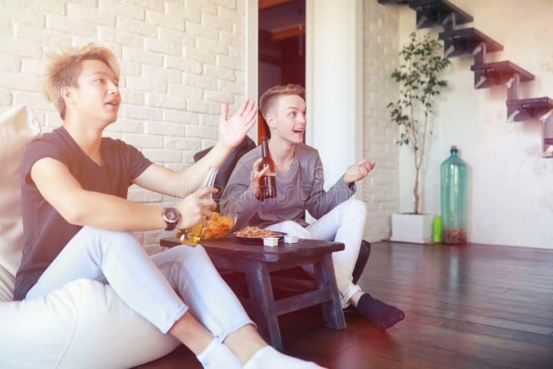 Mirando un partido de deportes con los amigos en casa imagenes de archivo
