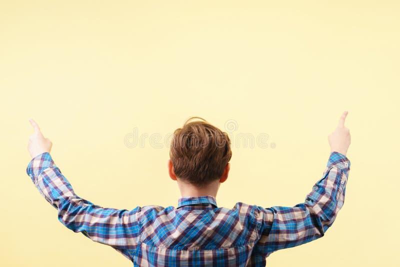 Mire allí puntos del muchacho hacia arriba con los dedos índices fotografía de archivo