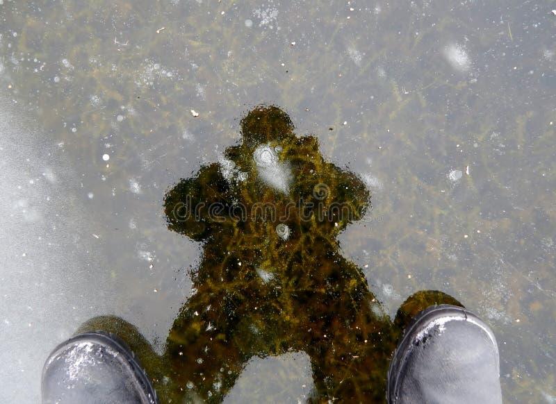 Mire con el grueso del hielo del lago foto de archivo