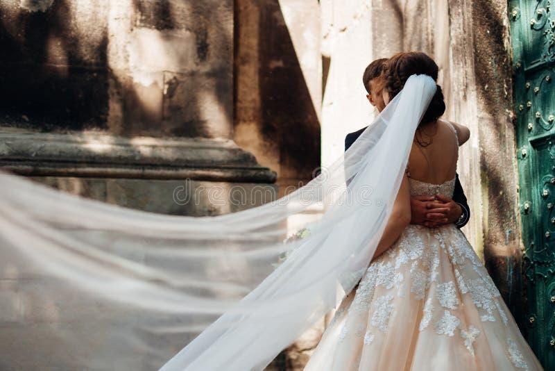 Mire el bride& x27; parte posterior de s de la cual vuela el velo mientras que ella abraza fotos de archivo