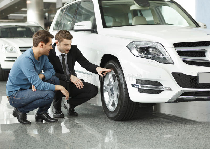 ¡Mire estos neumáticos! Vendedor de coches joven que muestra las ventajas o fotografía de archivo libre de regalías