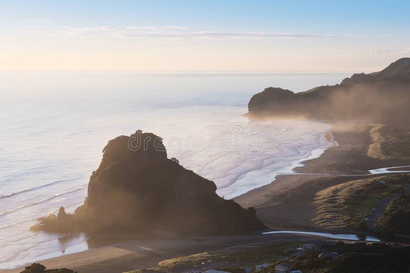 Mire hacia fuera a la opinión aérea de Lion Rock Piha Beach Auckland Nueva Zelanda de la playa de Piha cerca de Auckland La mayor imagenes de archivo
