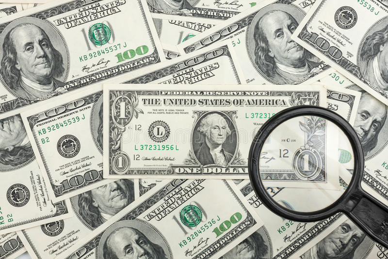 Mire a través de una lupa en el dinero foto de archivo libre de regalías