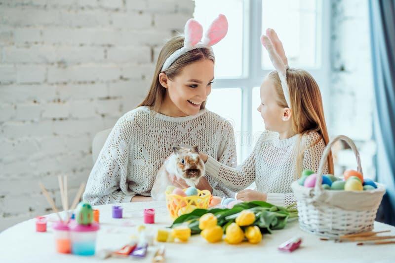 Mire un qué conejo lindo La pequeña hija con su movimiento de la madre un conejo decorativo casero imagen de archivo libre de regalías