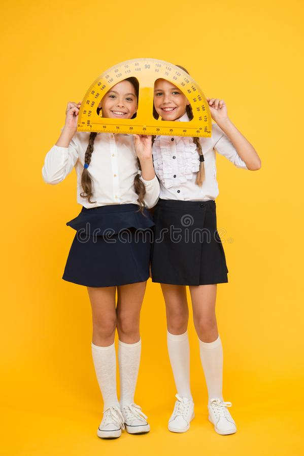 Mired in geometry. Maths and geometry. Kids in uniform at yellow wall. friendship and sisterhood. happy small girls. Study mathematics. students use protractor royalty free stock photos