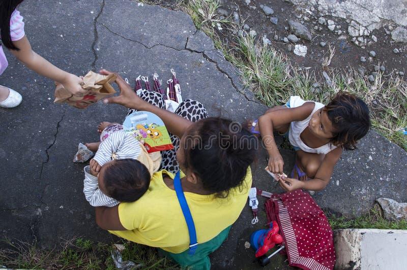 Mirez le bébé de caresse de femme de vendeur et un enfant recevant une poche de nourriture de par le passant photo libre de droits