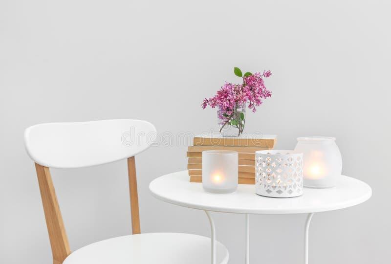 Mirez les lumières, les livres et les fleurs sur une table blanche photo stock