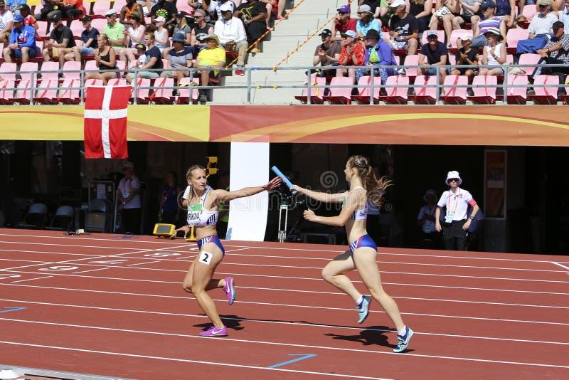 Miriam CIDORIKOVA och Sophia ZAPOTOCNA från den SLOVAKISKA REPUBLIKEN som kör relän för metrar 4x400 i IAAFEN royaltyfri foto