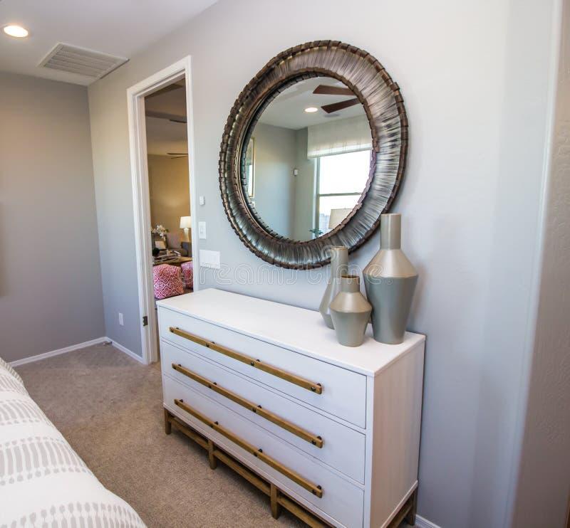 Miroir de chambre à coucher au-dessus de la raboteuse blanche photos libres de droits