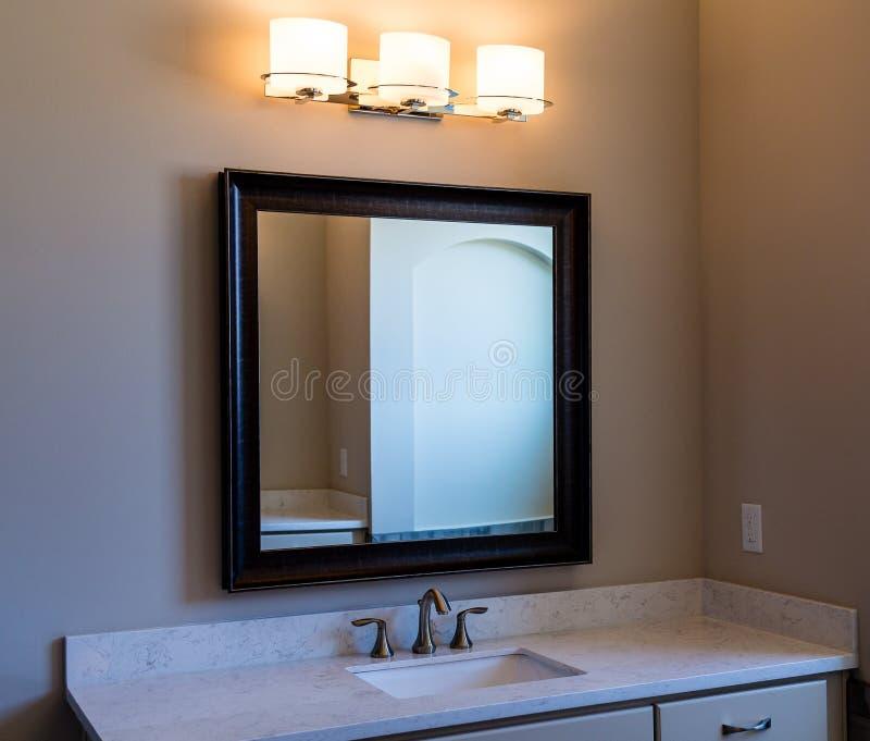 Miroir de coiffeuse et lumières modernes de salle de bains photos stock