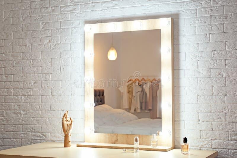 Miroir de maquillage sur la table près du mur blanc dans la chambre photo libre de droits