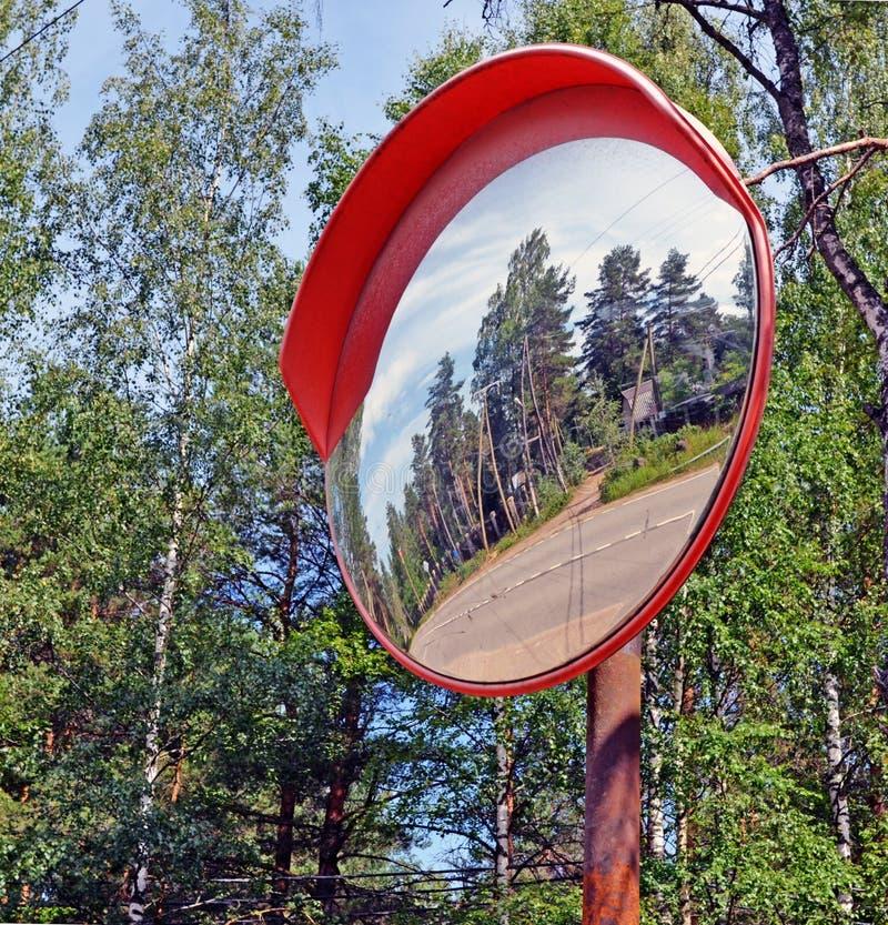 Miroir de sécurité se reflétant tordant la route image libre de droits