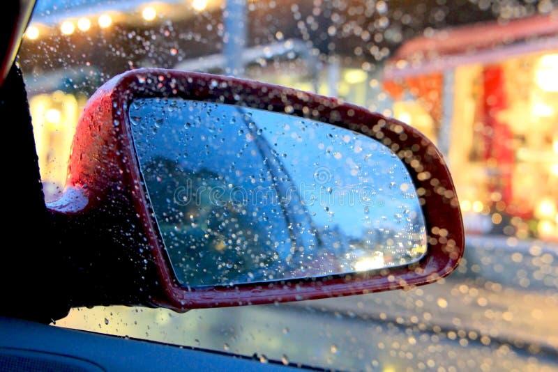 Miroir de vue de côté de voiture avec des baisses de pluie images stock