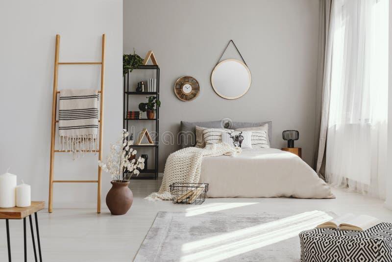 Miroir et horloge au-dessus de lit dans l'intérieur lumineux de chambre à coucher avec le pouf et fleurs à côté d'échelle photos stock