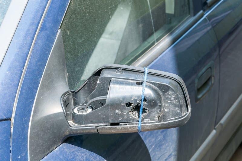 Miroir latéral cassé et endommagé sur les portières de voiture bleues avec les fils restants tenant le cadre en plastique sans ve photo libre de droits