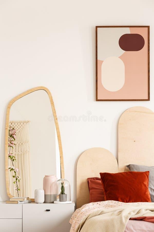 Miroir sur le coffret blanc à côté du lit avec les coussins rouges sous le courrier image stock