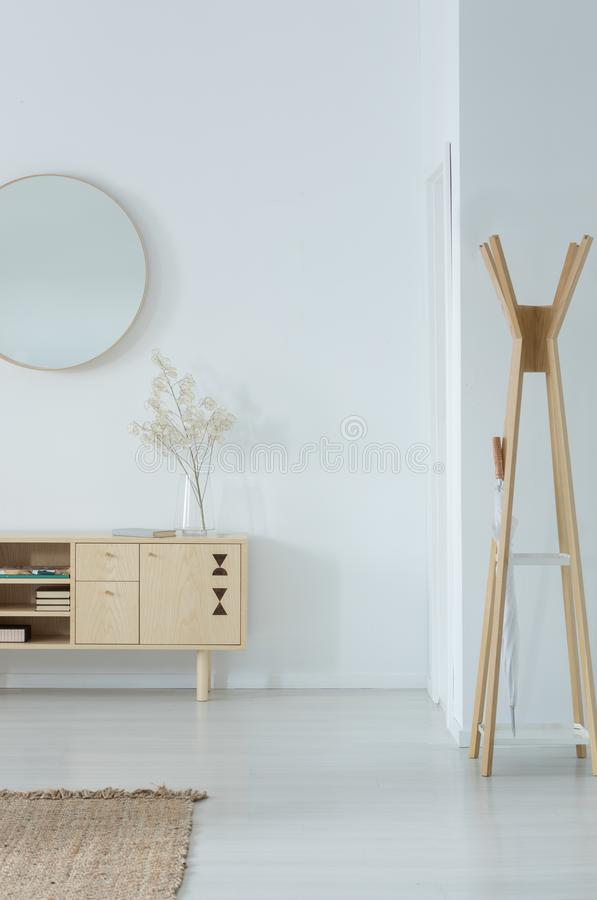 Mirror above stylish wooden cupboard with glass vase and flower on it, modern clothes hanger in the corner of white hall. Real photo with copy space stock photos