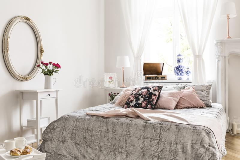 Mirror above white cabinet with roses in bedroom interior with p stock photography