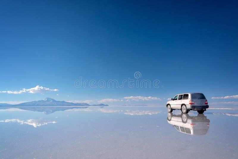 Mirror effect and reflections of a 4x4 car in Salar de Uyuni Uyuni salt flats, Potosi, Bolivia South America stock images