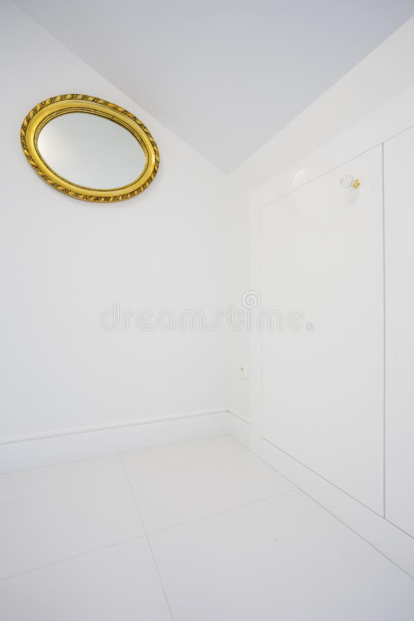 Mirror with golden frame. On white wall royalty free stock image