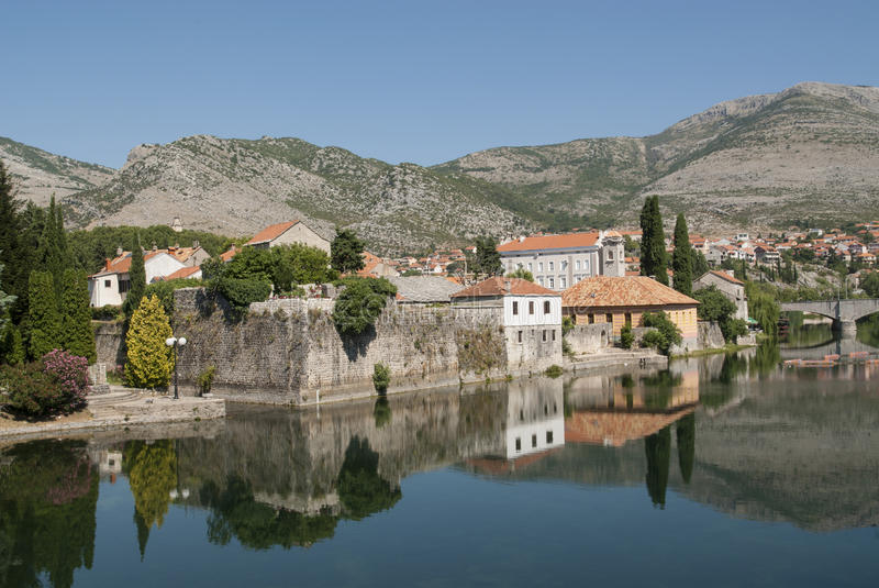 Mirror image of the old buildings in the town of Trebinje, Bosnia and Herzegovina in the water of the river. Mirror image of the old buildings in the town of stock images