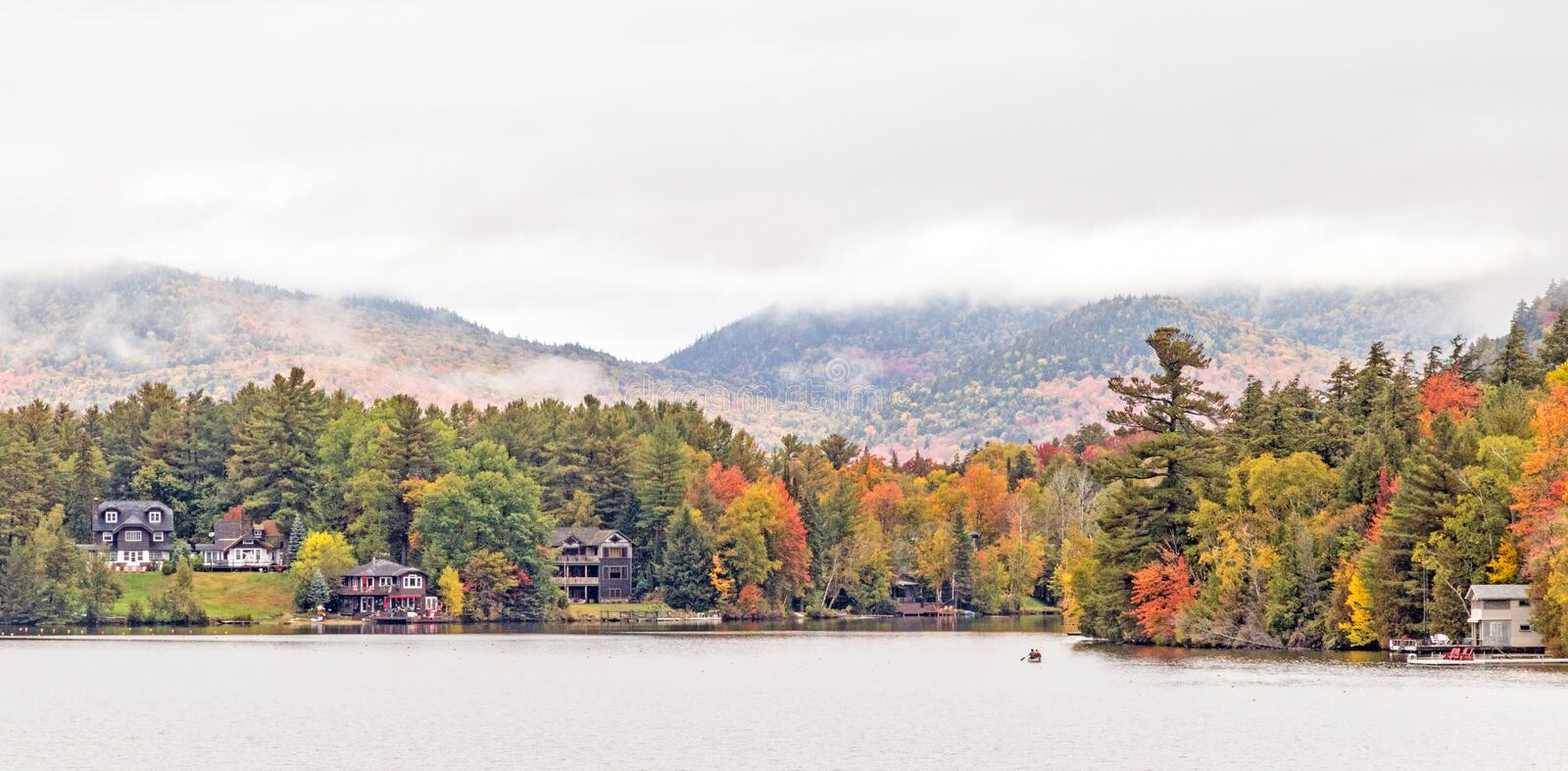 Mirror Lake in fog, Lake Placid. Homes and businesses on edge or shoreline of Mirror Lake in fog, Lake Placid village, New York in Autumn colors, Adirondack royalty free stock images