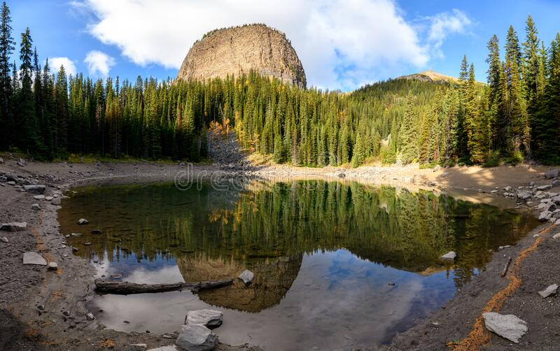 Mirror lake with pine forest reflection on pond in Lake Louise at Banff national park, Canada. Panorama of Mirror lake with pine forest reflection on pond in stock photos