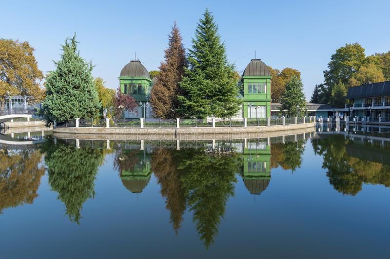 Mirror lake and the reflections of autumn trees and the Viennese pavilion in it. International Fair, Plovdiv, Bulgaria royalty free stock images