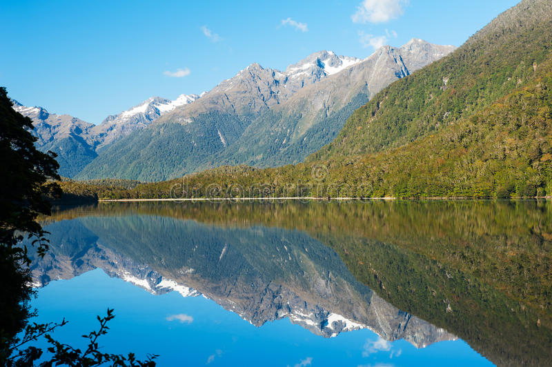 Mirror Lakes. Are a famous natural landmark omn the Milford Road in the Fiordland National Park. Snowy mountains are reflecting in a calm water. New Zealand royalty free stock photo
