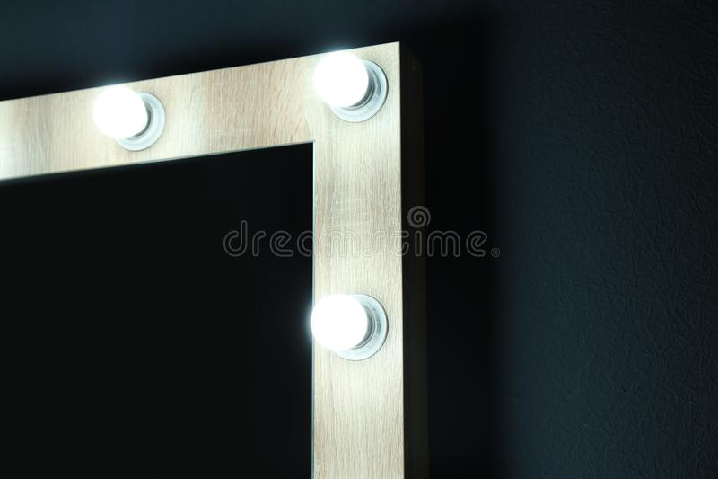 Mirror with light bulbs on color wall, closeup view with space for text. Dressing room royalty free stock photo