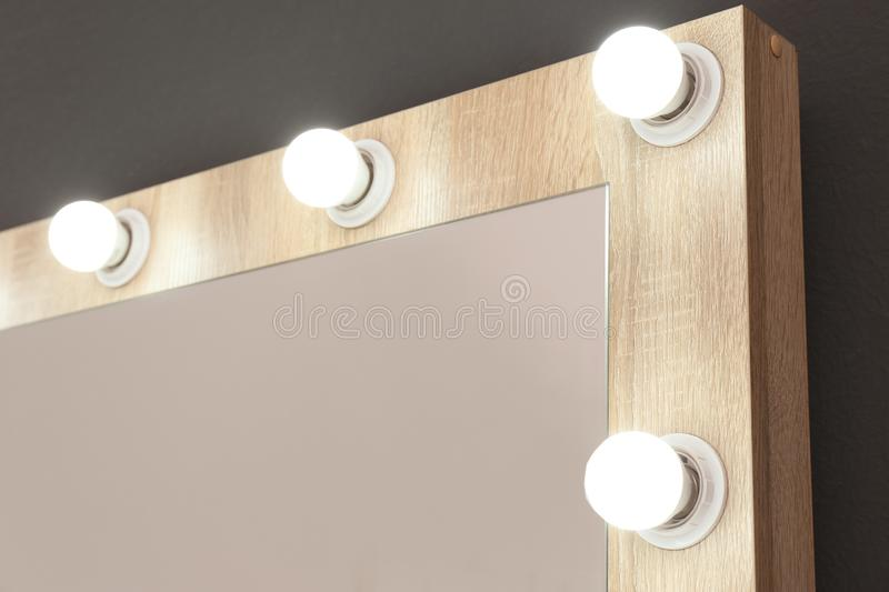 Mirror with light bulbs on grey wall, closeup. Dressing room stock photos