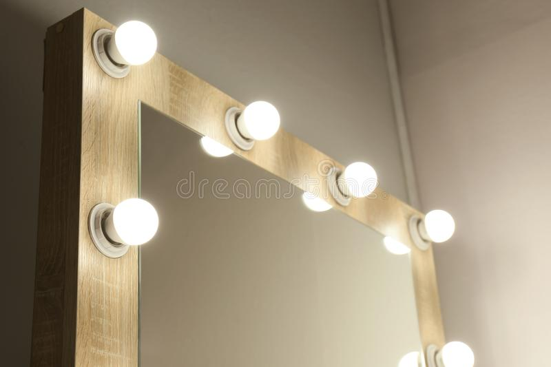 Mirror with light bulbs on white wall, closeup. Dressing room stock image