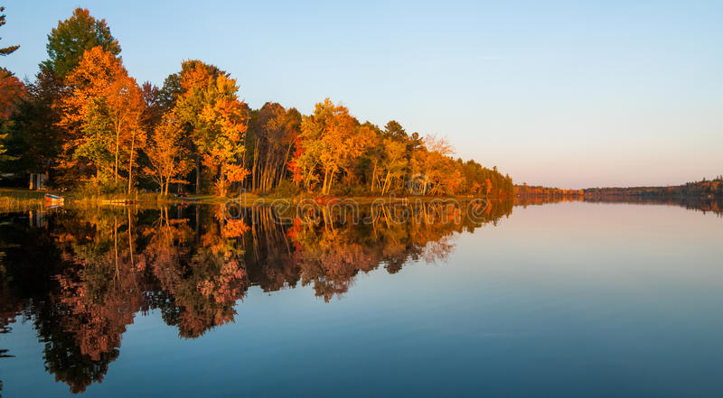 Mirror-like reflections and glowing orange forest on a Northern Ontario lake at sundown on a late summer's day. A warm September evening after a likewise day on royalty free stock images