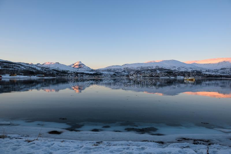 Mirror-like reflections in a Norwegian fjord near Tromsø. Norway just before sunset stock photography