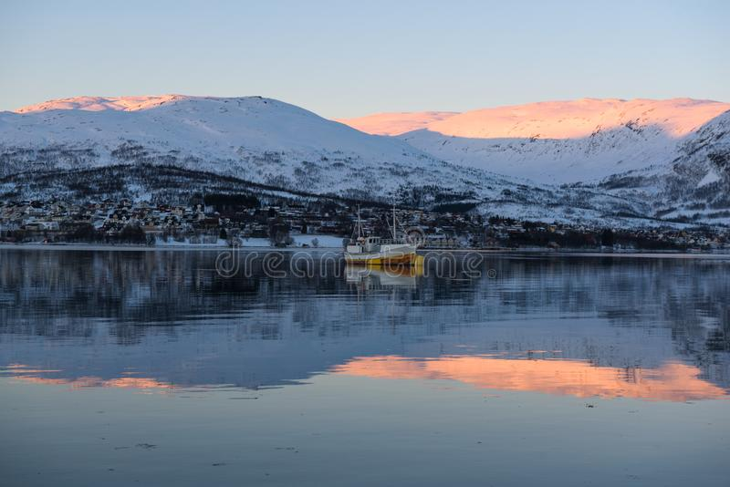Mirror-like reflections in a Norwegian fjord near Tromsø. Norway just before sunset stock photos