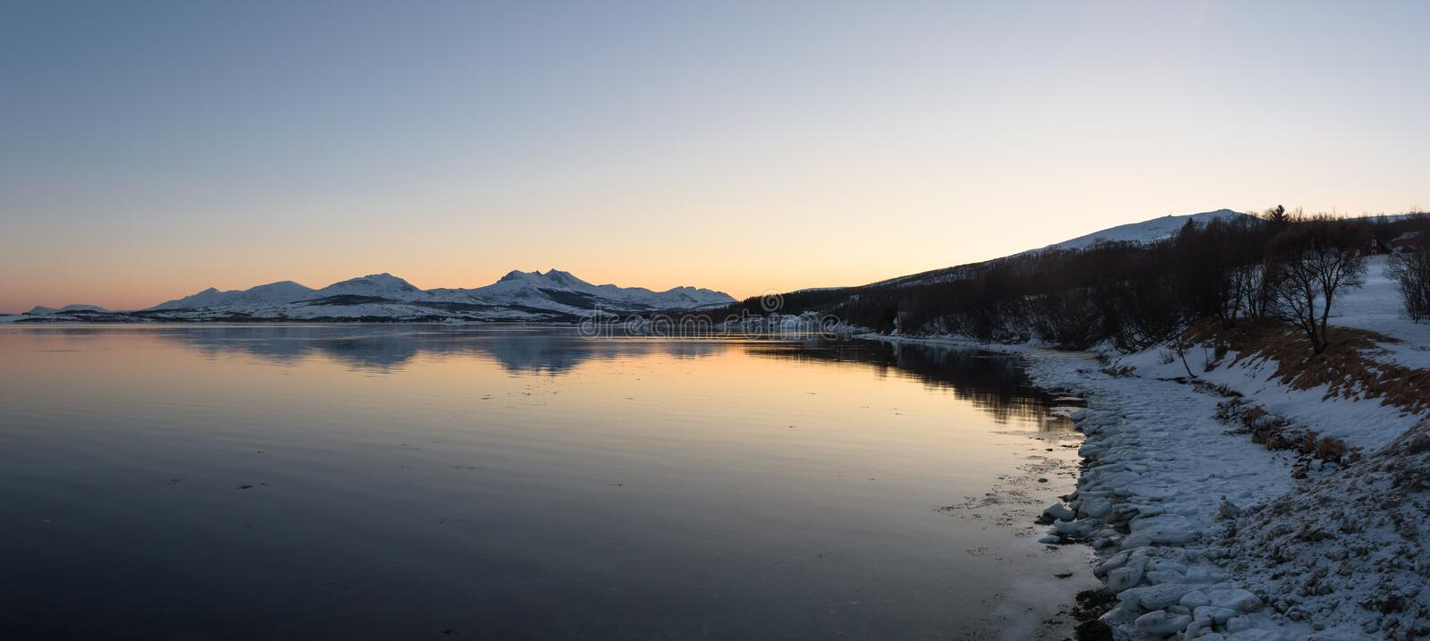Mirror-like reflections in a Norwegian fjord near Tromsø. Norway just before sunset royalty free stock photography