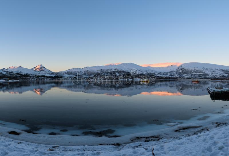Mirror-like reflections in a Norwegian fjord near Tromsø. Norway just before sunset stock image