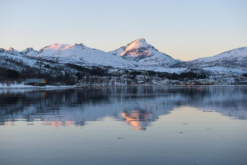 Mirror-like reflections in a Norwegian fjord near Tromsø. Norway just before sunset royalty free stock photo