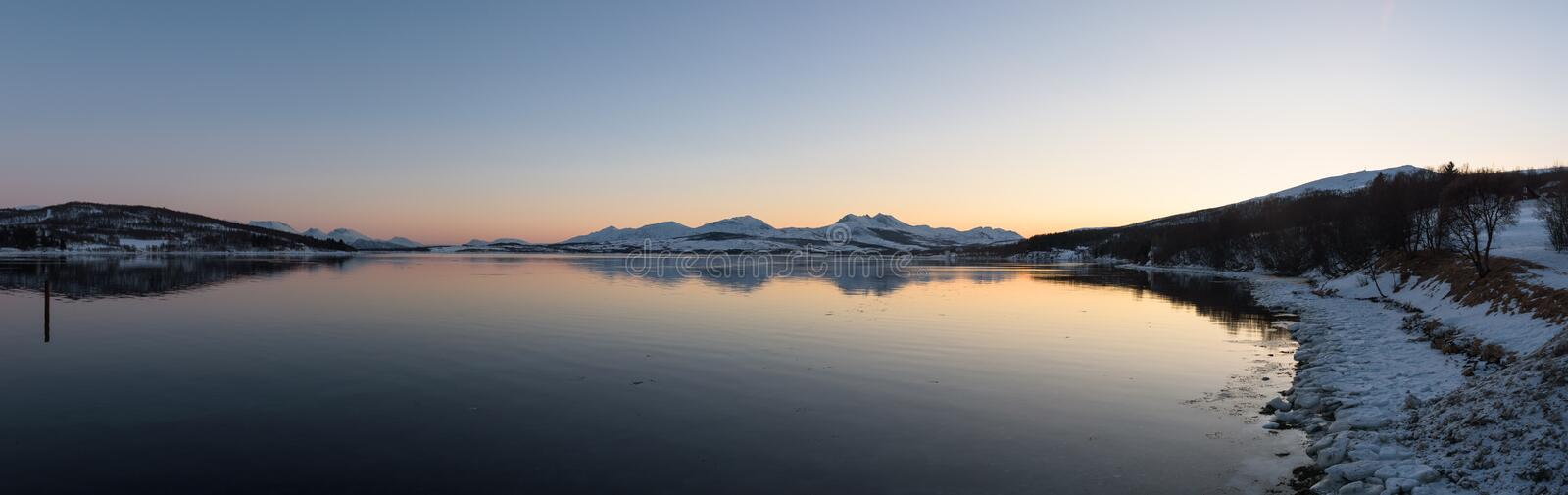 Mirror-like reflections in a Norwegian fjord near Tromsø. Norway just before sunset stock photo