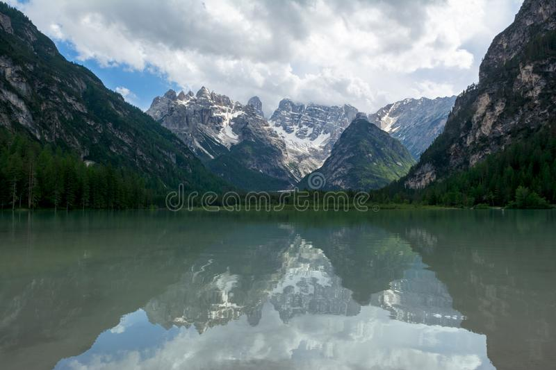Mirror-like surface of Lago Di Landro, Dolomites, Italy. Reflections of surrounding mountains and clouds in the water royalty free stock image