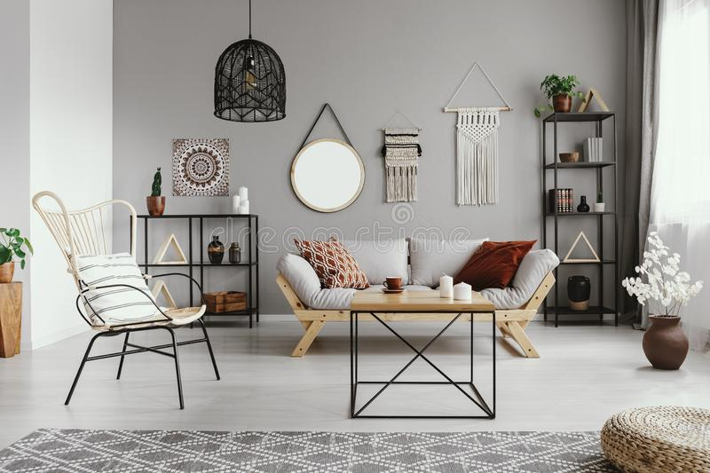Mirror, macrame and graphic on the grey wall of warm ethno living room royalty free stock images