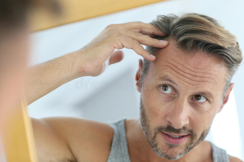 Mirror portrait of man concerned by hair loss stock photos