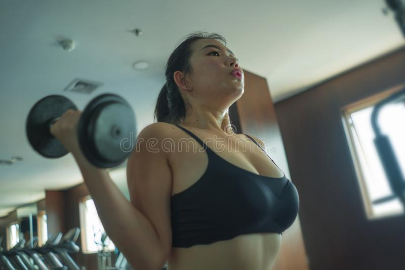 Mirror portrait of young pretty and fit Asian Chinese woman working hard at hotel gym or fitness center lifting dumbbell doing. Body building indoors workout in stock images