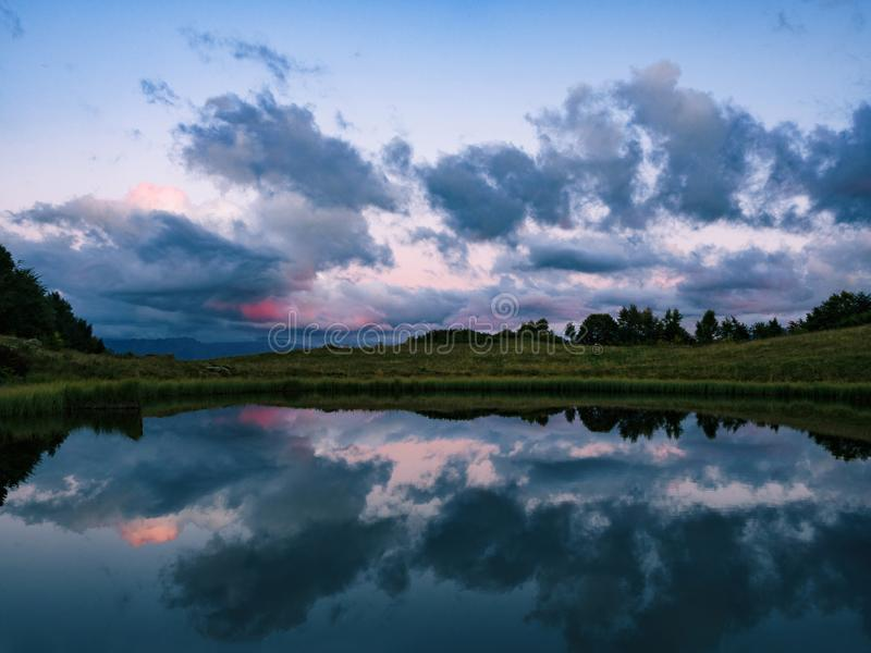 Mirror reflection of clouds on lake water royalty free stock images