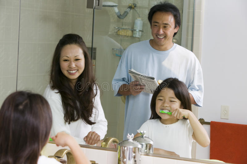 Download Mirror Reflection Of Family In Bathroom Getting Ready For Day Daughter Brushing Teeth Stock Image - Image: 30838499