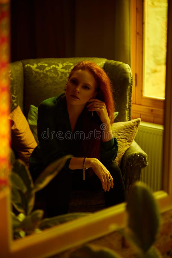 Vintage photo of Beautiful red haired young woman posing in old loft apartment in Tbilisi. Mirror reflection of Ginger lady posing in loft apartment in Tbilis royalty free stock photo